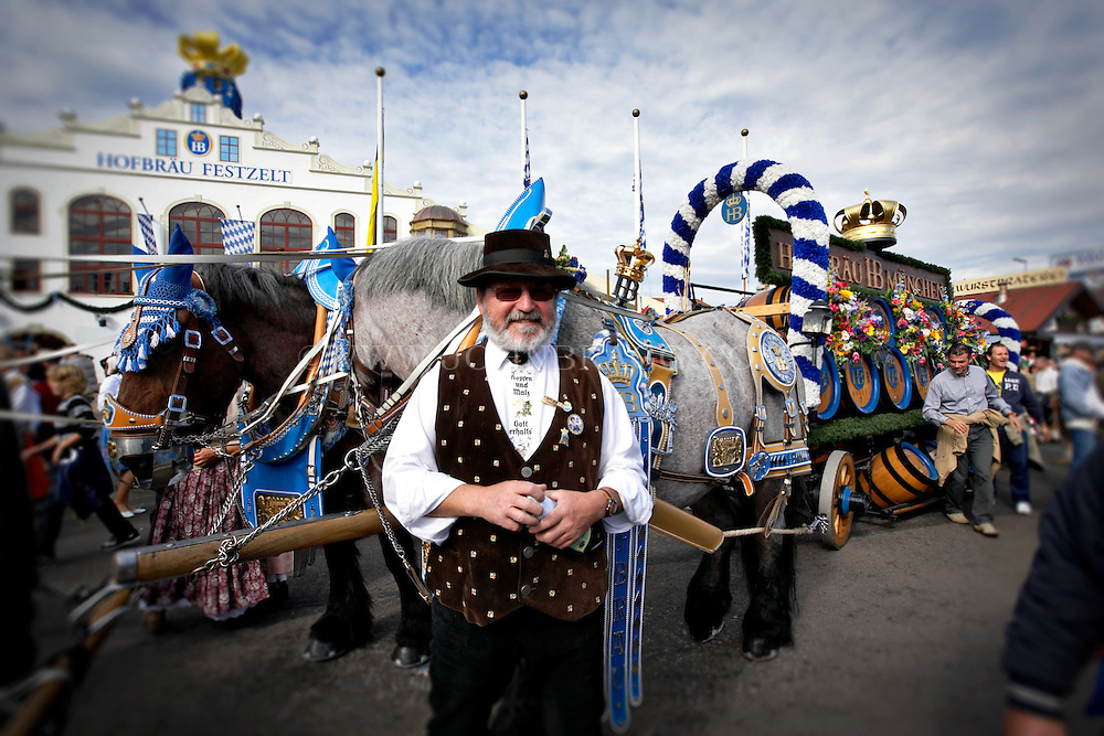 A man dressed for Oktoberfest, outside of the Hofbrau Tent,horses pulling a beer cart, Munich, Germany.
