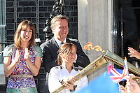 LONDON - JULY 26: Prime Minister David Cameron and wife Samantha along with 300 London school children greeted the Olympic flame in Downing Street, London, UK. July 26, 2012. (Photo by Richard Goldschmidt)