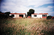 Abandonned prefabs in Newport, 2003. Thousands of post-war prefabs are still being lived in and cherished by their tenants or owners all over the UK. I  love prefabs. Some people will think living in a prefab is like living in a box. Yes, it might sound or even look a bit like that but what a lovely, sophisticated box! I am talking about post-war prefabs, erected in a hurry just after the war when Britain was suffering an unprecedented housing shortage. More than 150 000 of these prefabricated houses were erected all over the UK mainly ins small estates. They were luxury to most of the residents who mainly were service men coming back from the war and reuniting with their family. Their prefab became their little castle with all mod cons and even more than any working class could hope for at the time: hot water, toilets inside, a fitted kitchen with a gas fridge and a garden all around the house. Part of the temporary housing programme, they were not supposed to last over a decade. Yet, over 70 years later, a few Thousands are still standing and very much loved.<br />