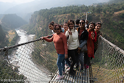 A Nepali family on the Kusma Gyadi Bridge, the tallest (443') and one of the longest (1,128') suspension bridges in the country, on Day-7 of our Himalayan Heroes adventure riding from Tatopani to Pokhara, Nepal. Monday, November 12, 2018. Photography ©2018 Michael Lichter.