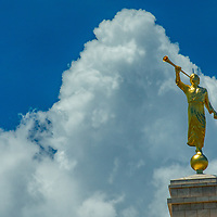 Clouds swirly around a statue of the angel Moroni, atop the Mormon church in Monticello, Utah.