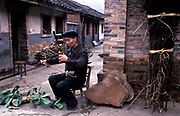Chen Yi He, Chinese Herbalist, relaxing as he plays the peaceful  traditional Erhu instrument at home, Xiao Meng Yang town, Yunnan province, China.