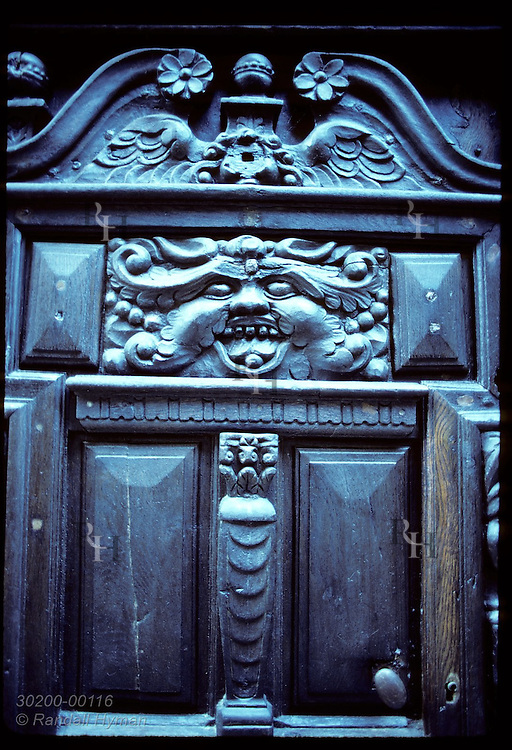 Detail of fanciful face carved on wooden door in city of Saint Malo. France
