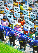 """Protesting Toy Action Figures on sidewalk with """"No!"""" banners and Riot Police in foreground."""
