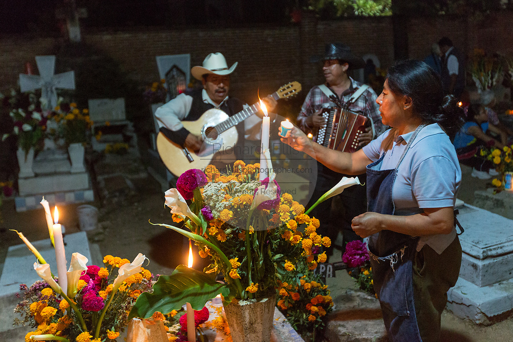 A Mexican woman lights a candle at the gravesite of relatives as a mariachi band plays for Day of the Dead festival known in Spanish as Día de Muertos at the old cemetery October 31, 2013 in Xoxocotlan, Mexico.  The festival celebrates the lives of those that died.