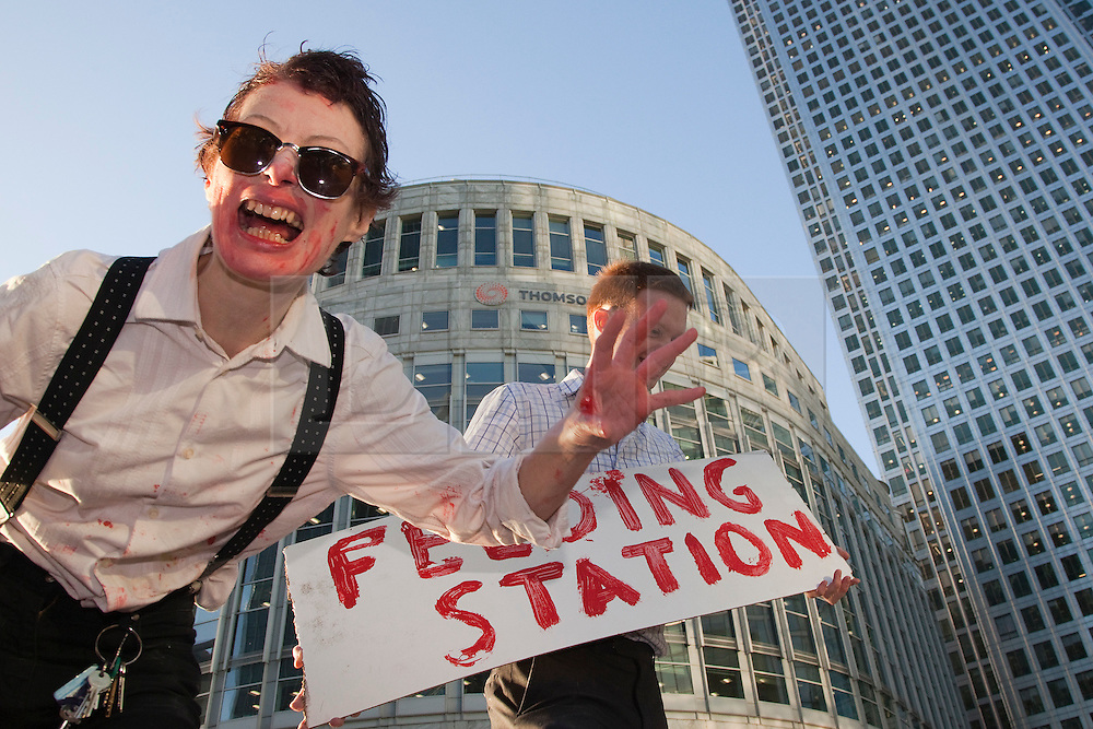 """© Licensed to London News Pictures. 12/09/2011. London, UK. A flashmob consisting of """"zombie bankers"""" looking for blood descended upon """"public sector workers"""" in Canary Wharf to bleed them dry. The """"feeding frenzy"""" in Canary Wharf was organised on Facebook by the """"Department of Corporate Sustenance"""" and involved around 30 volunteers who turned into bankers and victims for the event. The entire event was intensely watched by Police and Canary Wharf Security alike. Photo credit: Bettina Strenske/LNP"""