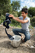 Calais August 2015 The Jungle, camp of migrants, most of whom are trying to get to England. A 15 year old Afghan boy washes his clothes.