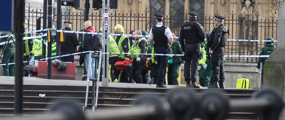 London, March 22nd 2017. Paramedics and fire officers remove a casualty from Westminster Bridge in the aftermath of a shooting incident on Westminster Bridge, where several pedestrians were also mown down by a car.
