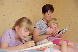 Mother reading with daughter in bedroom; older sister lying on bed drawing in colouring book,