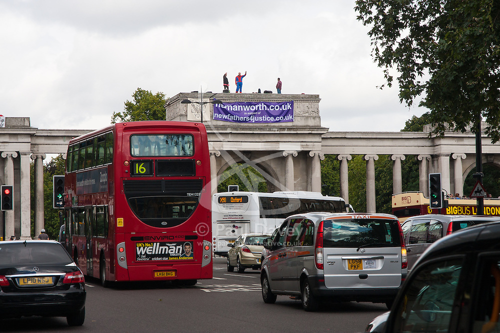 """London, August 12th 2014. Protesters from Fathers For Justice, atop Decimus Burton's Ionic screen entrance to Hyde Park adjacent to Apsley House at  Hyde Park Corner,  """"protest to highlight the injustice fathers face in the present family court system""""."""