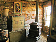 """A Chinese portrait hangs by an old wood stove and boxes in a frontier cabin built in 1890 in Butte and moved to the outdoor history museum of Nevada City, Montana, USA. In 1870, Chinese people (nearly all male) made up 10% of the territorial population of Montana. Territorial laws prohibited """"China Men"""" from owning placer claims, so they mined the leavings of others or performed laundry or domestic service, which was always in great demand. Today Nevada City contains several fascinating Chinese buildings built about 1890, mostly moved here from Butte, Montana. Nevada City was a booming placer gold mining camp from 1863-1876, but quickly declined into a virtual ghost town. This fascinating town inspires you to imagination what life must have been like in early Montana when gold was discovered at nearby Alder Gulch. More than 90 buildings from across Montana have been gathered for preservation at Nevada City, mostly owned by the people of the State of Montana, and managed by the Montana Heritage Commission. In 2001, the excellent PBS television series """"Frontier House"""" used one of the buildings and its furnishings to train families in re-creating pioneer life. A miner's court trial and hanging of George Ives in the main street of Nevada City was the catalyst for forming the Vigilantes, a group of citizens famous for taking justice into their own hands in 1863-1864. Directions: go 27 miles southeast of Twin Bridges, Montana on Highway 287."""