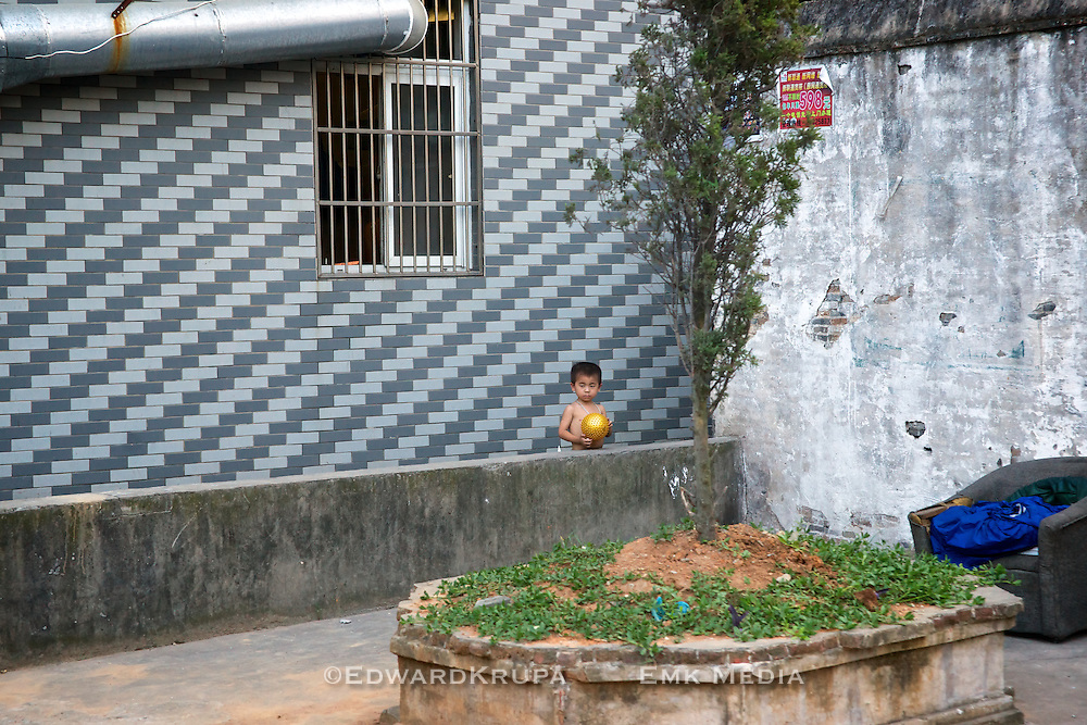 Boy standing in an outdoor courtyard, Wenzhou, China.