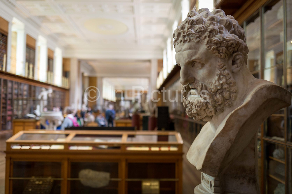 The bust of mythical Hercules, a Roman copy of the ancient Greek original by Lysippos of about 325-300BC overlooks the Enlightenment Gallery of the British Museum on 28th February 2017, in London, England. The Roman version is said to have been found in lava at the foot of Vesuvius and presented to the museum by Sir William Hamilton in 1776. Hercules is the Roman adaptation of the Greek divine hero Heracles,  the son of Zeus Roman equivalent Jupiter and the mortal Alcmene. In classical mythology, Hercules is famous for his strength and for his numerous far-ranging adventures.