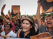 """19 SEPTEMBER 2015 - BANGKOK, THAILAND:  Anti-coup protestors march to Democracy Monument during a rally against the military government. The sign they are carrying says, """"Let's Declare Victory and Step Over Dictatorial Power."""" Hundreds of people protested against Thailand's military dominated government Saturday. The protest started with seminar about the 2006 coup that deposed popularly elected former Prime Minister Thaksin Shinawatra. After the seminar activists marched from Thammasat University to Democracy Monument, about 1 mile. Political gatherings of more than 5 people are banned by Thailand's military government and police tried to dissuade the protestors from finishing their march. Protestors ignored the police, who then stood by and watched but made no effort to intervene. At Democracy Monument protestors laid flowers and made speeches against the military. It was the largest anti-coup protest in Bangkok in more than a year.    PHOTO BY JACK KURTZ"""
