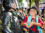 "15 JUNE 2014 - BANGKOK, THAILAND:  A woman makes a heart with her hands after posing for photos with Thai military special operations soldiers during public relations ""Return Happiness to Thais"" party in Lumpini Park in Bangkok. The Thai military junta, formally called the National Council for Peace and Order (NCPO), is sponsoring a series of events throughout Thailand to restore ""Happiness to Thais."" The events feature live music, dancing girls, military and police choirs, health screenings and free food.  PHOTO BY JACK KURTZ"