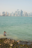 A man from south Asia, living in Doha, Qatar for work, clears rocks from the sea to deepen the water for parking a dhow.