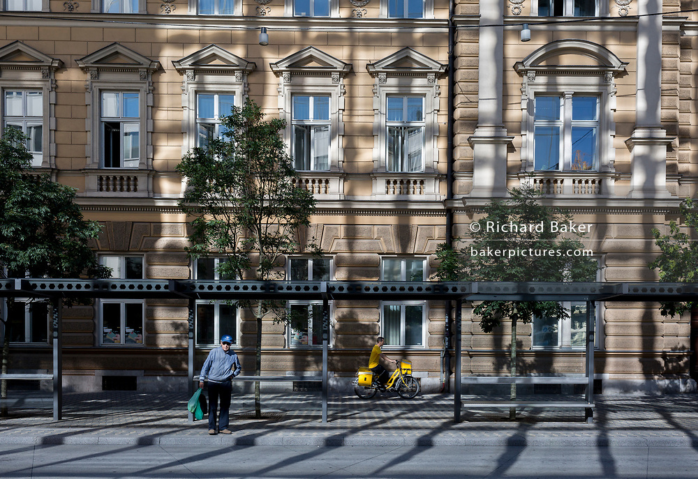 A pedestrian and cyclist for the Slovenian postal service (Posta Slovenije) outside the main post office on Slovenska Cesta (street) in the Slovenian capital, Ljubljana, on 25th June 2018, in Ljubljana, Slovenia.