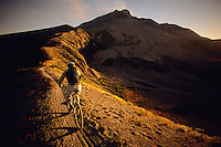 A mountain biker rides the Windy Ridge trail at sunset in the Mount St. Helens N.V.M., Washington.