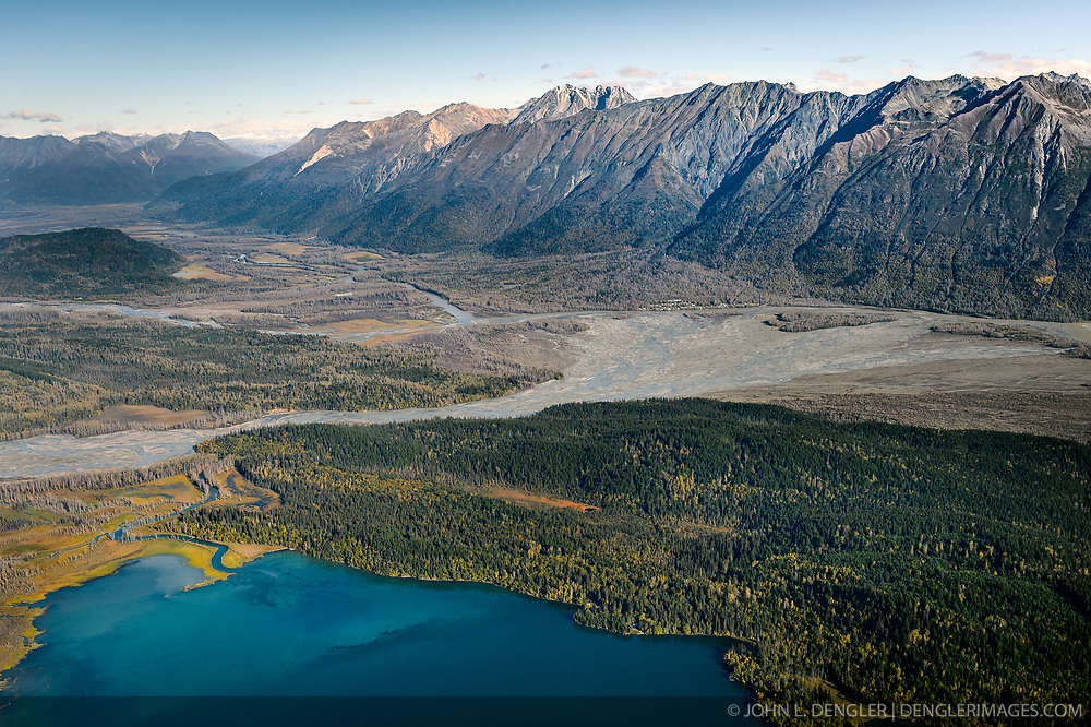 """This aerial photograph of a portion of the """"Council Grounds"""" is the primary area where bald eagles gather on the Chilkat River in the Alaska Chilkat Bald Eagle Preserve near Haines, Alaska. Bald eagles come to the alluvial delta area at the confluence of the Tsirku (center) and Chilkat (upper left to right) Rivers because of the availability of spawned-out salmon and open waters in late fall and early winter. The open water is due to a deep accumulation of gravel and sand that acts as a large water reservoir whose water temperature remains 10 to 20 degrees warmer than the surrounding water temperature. This warmer water seeps into the Chilkat River, keeping a five mile stretch of the river from freezing. Photographers come to the Chilkat River in November and December to photograph one of the largest gatherings of bald eagles in the world. In 1982, the 48,000 acre area was designated as the Alaska Chilkat Bald Eagle Preserve. In the background are the mountains that make of the Takshanuk Mountains. Chilkat Lake is pictured in the foreground. River on the left above the Tsirku River is the Klehini River which joins the Chilkat River right before the Tsirku River alluvial fan. Also pictured is Klutshah Mountain (top center), Iron Mountain and the village of Klukwan (in front of the left side of the alluvial fan)."""