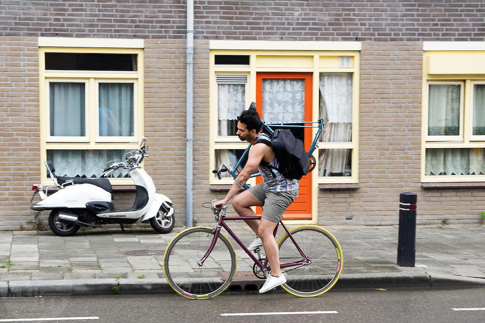 In Utrecht rijdt een man op een fixie met een fietsframe om zijn schouder.<br /> <br /> In Utrecht a man is cycling on a fixed gear bicycle with a frame on his shoulder.
