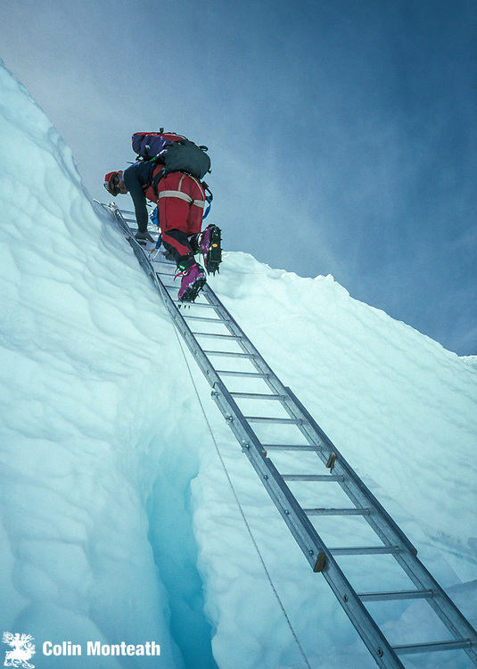 New Zealand mountaineer Gary Ball climbs a ladder over a large crevasse in Khumbu icefall, during climb of Chomolungma, Mt Everest, Nepal, Himalaya