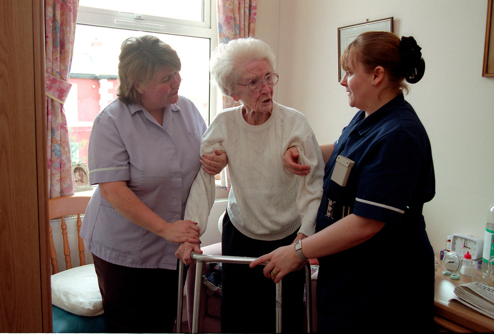 Nurse and trainee nurse helping older woman to walk in old people residential home,
