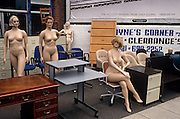 From the side of a road in south London, we see a group of naked female mannequins, standing and sitting with furniture on the forecourt of an office supplies business. A clearance sign stands partly-obscured but one's attention is to the physiques of each model that tends to signify whichever the fashion industry has decreed is the 'look' of the decade - whether buxom or skinny - and shop windows are therefore occupied with the clothing shapes of the day. Some women stand in that classic fashion pose, with arms at the side and one leg in front of the other, or sitting with one leg elegantly crossed: All designed to make the clothes they wear look attractive.