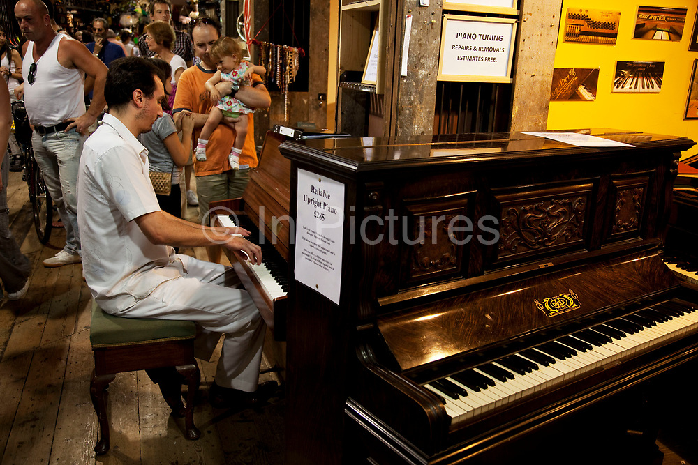 Man playing the piano in Horse Tunnel Market at Camden Market, North London. Camden Lock is a crowded hang out for young Londoners.