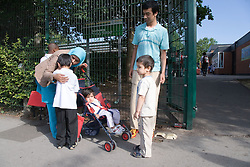 Young family saying goodbye to child at school gates