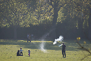 In the third week of the UK government's lockdown during the Coronavirus pandemic, when the daily UK death rate rose by another 761 to 12,868 and with nearly 100,000 reported cases. a man exhales bape smoke while taking daily exercise in Ruskin Park, a public green space in the south London borough of Lambeth, on 15th April 2020, on 15th April 2020, in London, England.