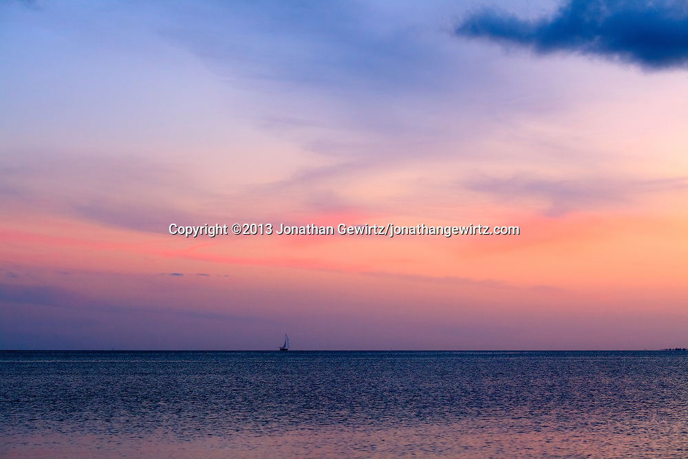 A sailboat cruises at twilight on Biscayne Bay just south of Key Biscayne, Florida. WATERMARKS WILL NOT APPEAR ON PRINTS OR LICENSED IMAGES.