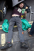 An environmental activist from Extinction Rebellion uses a lock-on under a vehicle to block a road in the Covent Garden area during the first day of Impossible Rebellion protests on 23rd August 2021 in London, United Kingdom. Extinction Rebellion are calling on the UK government to cease all new fossil fuel investment with immediate effect.