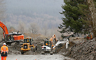 Heavy equipment works through the meters high mud covering highway 530 at the mudslide in Oso, Washington March 30, 2014. Local churches offered prayers on Sunday for the victims of last week's devastating mudslide in Washington state and words of solace for grieving families and friends, many of whom are still waiting for news of missing loved ones.  REUTERS/Rick Wilking (UNITED STATES)