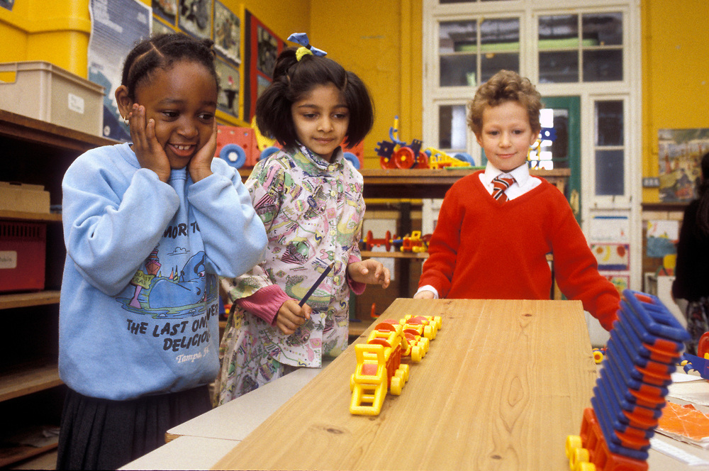 Small group of primary age children experimenting with motion in science class,
