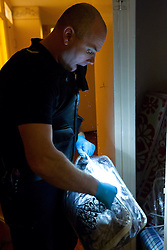© Licensed to London News Pictures.  06/12/2012. MILTON KEYNES, UK. COLLECT PHOTO FROM TVP. A Thames Valley Police officer searches a house as part of Operation Rouse. A total of 22 warrants were executed under the Misuse of Drugs Act in the Milton Keynes area this morning, with a further four carried out in the Metropolitan Police area and one in Northampton. 240 police officers were involved and 21 people arrested. A quantity of drugs, cash and weapons were seized. Photo credit :  TVP/LNP