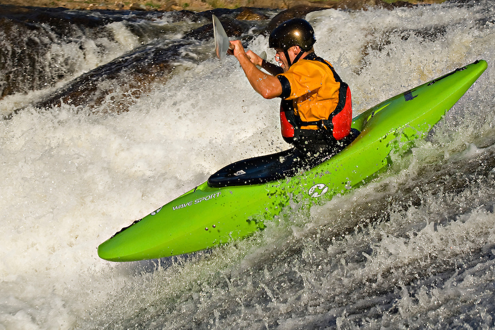 A whitewater kayaker descends a waterfall on the Dead River near Marquette Michigan.