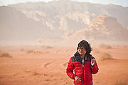 SeongRyeong Bak walks smoking a cigarette down a Jeep track through the red sand desert of Wadi Rum, Jordan