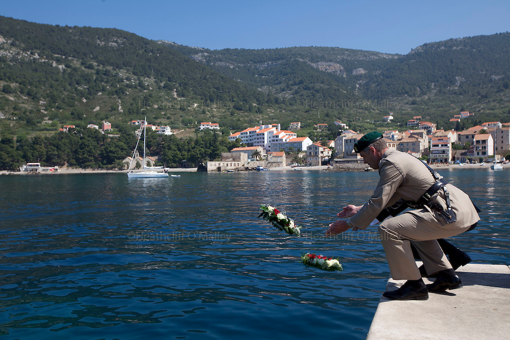 Mcc0031516 . Daily Telegraph..A commemorative wreath is thrown into the Adriatic sea by Col Kevin Oliver RM off the jetty in the fishing town of Komiza on the island of Vis where British forces were based during WWII .. A reunion of British WW2 Veterans, probably for the last time. They are some of the last survivors of an Allied combined garrison of Royal Navy, Royal Marine Commandos, Army and Royal Air Force personnel who took over the Island of Vis in 1943 and held it until the end of the War. From here they harried Axis Forces in what was Yugoslavia, providing supply drops to the Partisans and, at one point, refuge for Marshall Tito when he was nearly captured by German Forces ...19 May 2011 Vis, Croatia