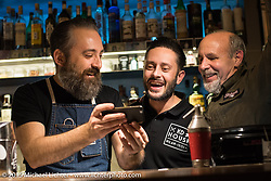 Bartenders Frank (bearderd guy) and Stefano with Michael Lichter at the KD House bar Saturday night after EICMA, the largest international motorcycle exhibition in the world. Milan, Italy. November 21, 2015.  Photography ©2015 Michael Lichter.