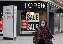© Licensed to London News Pictures. 26/12/2020. London, UK. Members of the public in masks walk past closed shops on Oxford Street, London on Boxing Day, one of the busiest shopping days of the year. A near deserted Oxford Street this afternoon as all non-essential shops remain closed due to the continuing coronavirus pandemic that has swept throughout the World. Last week Health Secretary Matt Hancock announced that yet another new Covid-19 mutation has been discovered in the UK as Downing Street orders many more areas of England to go into Tier 4 lockdown from today (Boxing Day) with tougher new Covid-19 restrictions for many as the mutated strains continue to spread throughout the UK. Photo credit: Alex Lentati/LNP