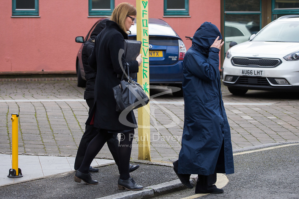 Accompanied by a liaison officer, family members of alleged burglar Henry Vincent, hiding their faces, leave the Inner London (South) Coroner's Court following a brief hearing. London, April 10 2018.