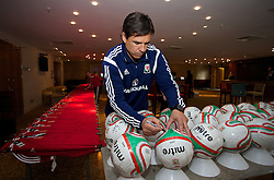 CARDIFF, WALES - Tuesday, March 4, 2014: Wales' manager Chris Coleman sign footballs during a signing session at the St. David's Hotel ahead of the International Friendly against Iceland. (Pic by David Rawcliffe/Propaganda)  CARDIFF, WALES - Tuesday, March 4, 2014: Wales' xxxx during a training session at the Cardiff City Stadium ahead of the International Friendly against Iceland. (Pic by David Rawcliffe/Propaganda)