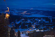 Skiers ascend chairlift for night skiing at Big Mountain resort in Whitefish Montana