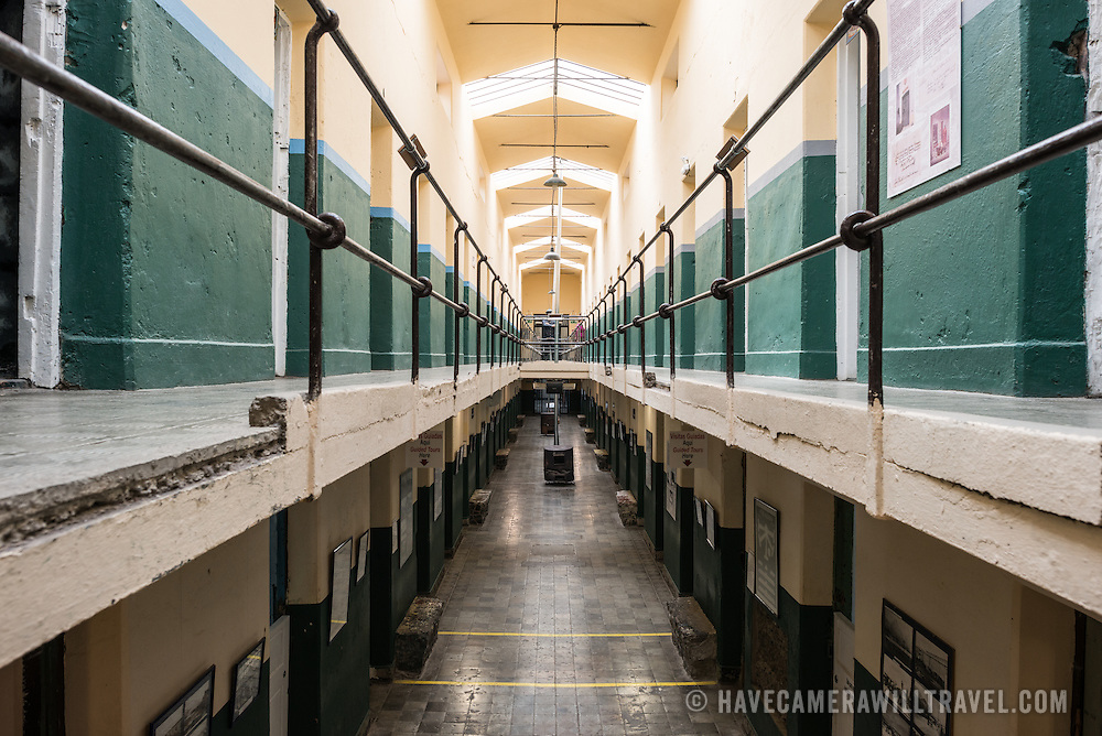 A two-level corridor lined with prison cells at the Maritime Museum of Ushuaia. The museum consists of several wings devoted to maritime history, Antarctic exploration, an art gallery, and a policy and penitentiary museum. The complex is housed in an historic prison building and uses the original cells and offices as exhibit spaces.