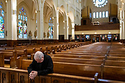 Rev. Bill Vanecko, a retired pastor, prays on Palm Sunday, April 5, 2020 during a live-streamed service in a nearly empty Saint Columbanus Catholic Church in Greater Grand Crossing during the coronavirus pandemic. (Brian Cassella/Chicago Tribune)