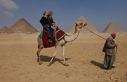 Tourists ride a camel next to the Great Pyramids of Giza. (Photo © Jock Fistick)