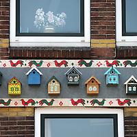 Nederland, Zaandam , 5 juli 2013.<br /> Wandeling door de binnenstad van Zaandam.<br /> Starten bij De Werf aan de Oostzijde. Daarvandaan kun je lopen op een soort boulevard tussen de flats en het water. De eerste stop is De Fabriek, filmhuis en eetcafé met terras aan de Zaan met uitzicht op de sluis. Daarna de sluis zelf.<br /> Dan langs het winkelgebied richting de Koekfabriek: Het oude Verkade pand dat is verbouwd en waar nu de bieb en sportschool en restaurant etc. in zitten.<br /> (Dat is aan de overkant van het startpunt) en misschien nog de Zwaardemaker meepakken aan de Oostzijde. Dat is een oud pakhuis die Rochdale enige jaren geleden heeft verbouwt tot appartementen met een stukje Nieuwbouw.<br /> Ook doen: het Russische buurtje vlakbij de Zaan. Dit jaar staat Rusland in de schijnwerpers en Zaandam heeft een speciale band met Rusland, vanwege het Czaar Peterhuisje en de Russische buurt. <br /> Op de foto: Datsja vogelhuiskes op gevel Hogendijk 76 in de z.g. Russische buurt.<br /> Foto:Jean-Pierre Jans