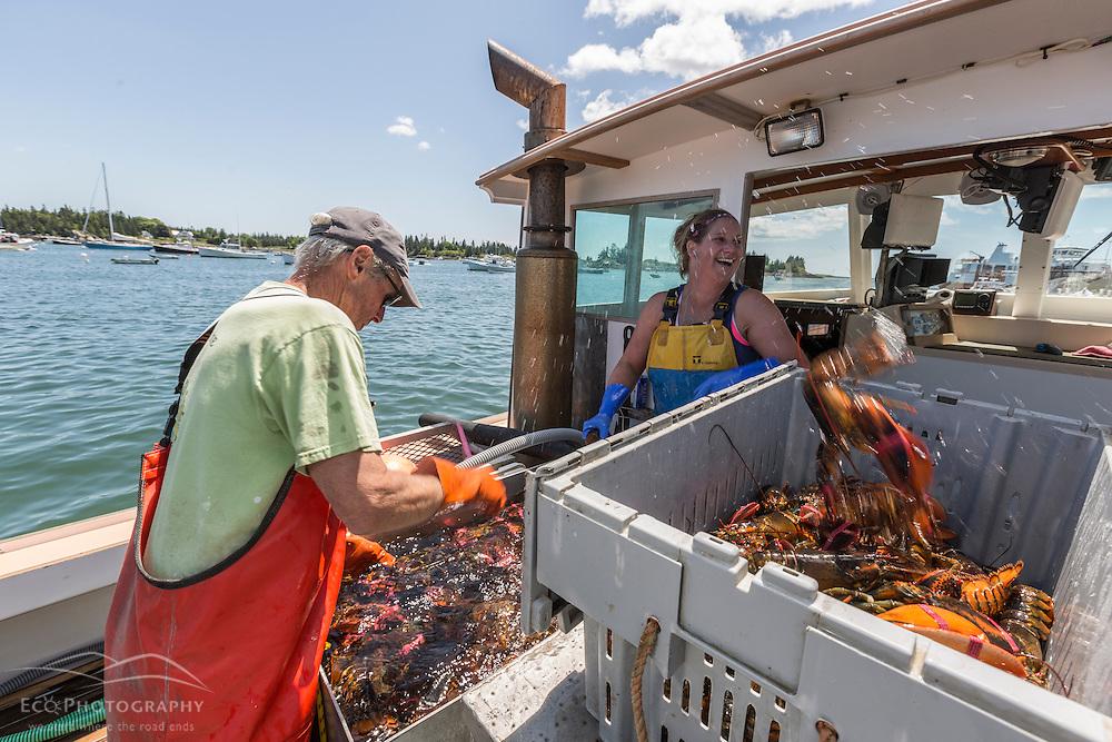 Captain Steve Rosen, and Stern Woman Kachina Watt unload lobsters aboard 'Star Fisher' at the Vinalhaven Fishermen's Co-op in Vinalhaven, Maine.