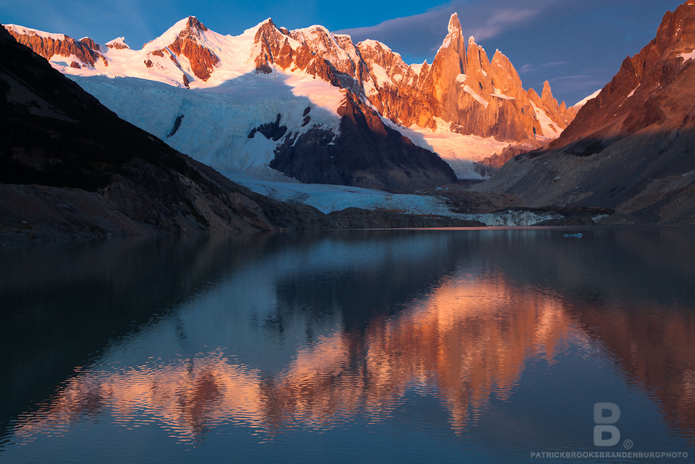 Golden mountain peak and light up with first light upon Cerro Torre and reflect in the lake below in Patagonia, Argentina.