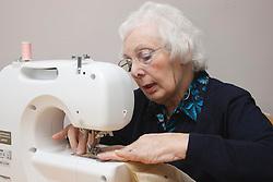 Elderly lady using sewing machine.